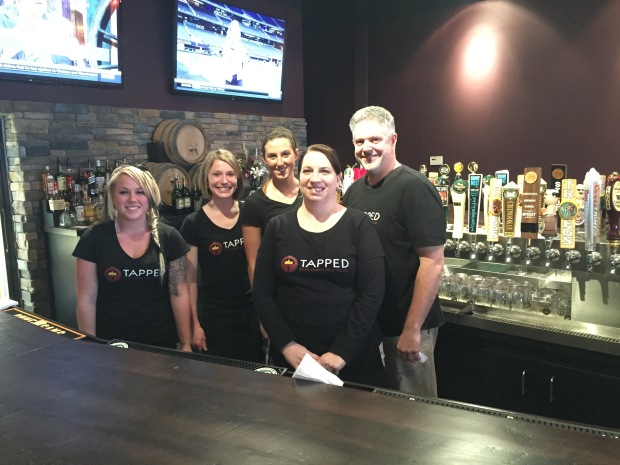 Tapped crew Caitlin Zakutney, Jenna Martin, Alyssa Liebdzinski, Bridget Noel, and Mike Kirk in front of the bar